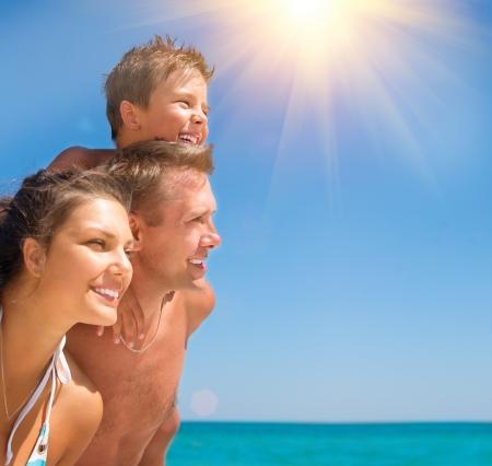 Feliz Familia joven con el pequeño niño que se divierte en la playa