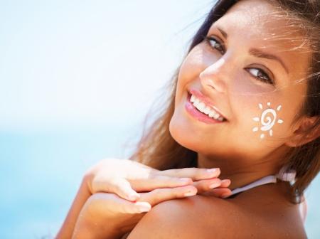 sol: Muchacha hermosa feliz aplicar crema solar Tan en su cara