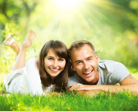 dientes sanos: Feliz pareja sonriente juntos Relajarse en la hierba verde al aire libre