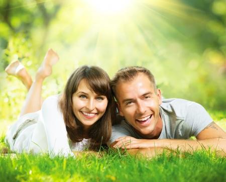 estilo de vida: Pares de sorriso felizes juntos relaxante na grama verde ao ar livre