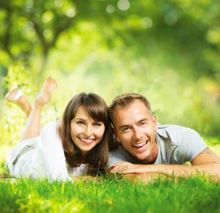 ao ar livre: Pares de sorriso felizes juntos relaxante na grama verde ao ar livre