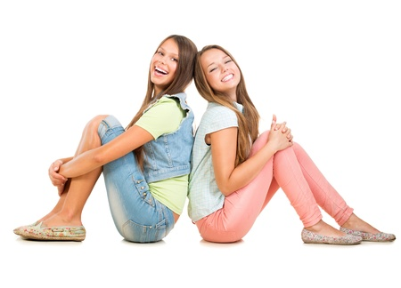 2 つの白い背景の友人に分離された 10 代の少女の笑顔