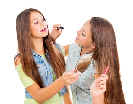 putting lipstick: Pretty Teenage Girls Applying Make up and Looking in the Mirror  Stock Photo