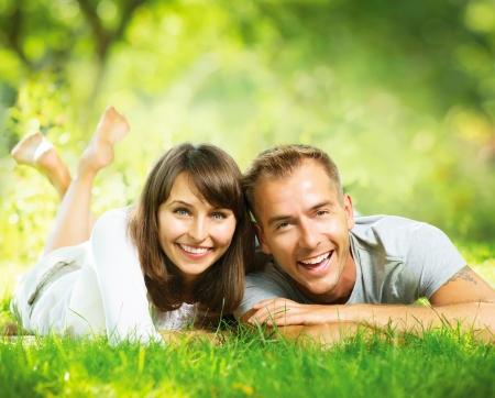 livsstil: Lycklig le Par avkopplande tillsammans på grönt gräs utomhus Stockfoto