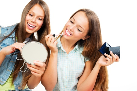 Pretty Teenage Girls Applying Make up and Looking in the Mirror  Imagens
