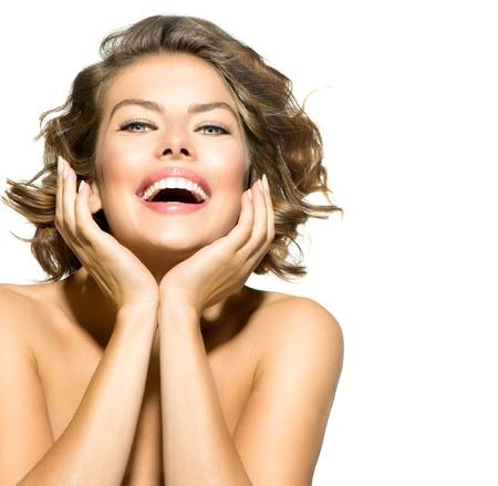 白い背景の上の若い女性の肖像画の笑顔の美しさ