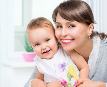 family baby: Happy Smiling Mother and Baby kissing and hugging at Home  Stock Photo
