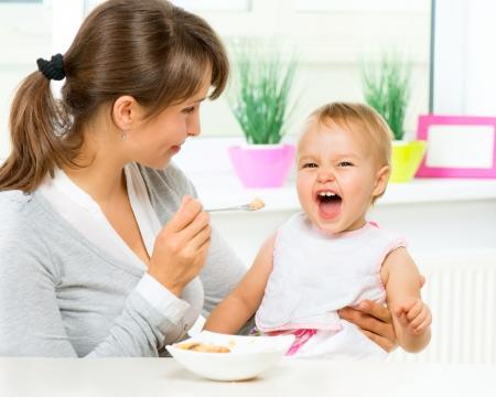 아기: 어머니는 숟가락으로 그녀의 여자 아기를 먹이는 스톡 콘텐츠
