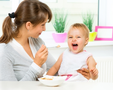 playing with spoon: Mother Feeding Her Baby Girl with a Spoon