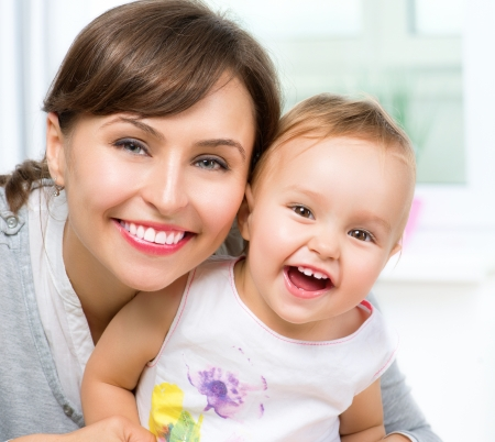 smiling teeth: Happy Smiling Mother and Baby kissing and hugging at Home  Stock Photo
