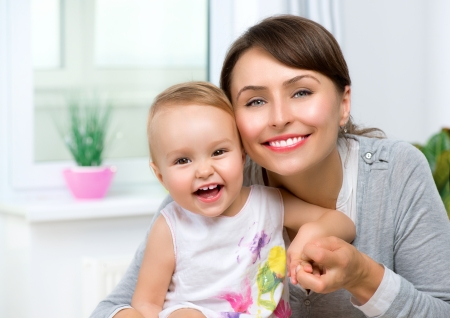 women hugging: Happy Smiling Mother and Baby kissing and hugging at Home