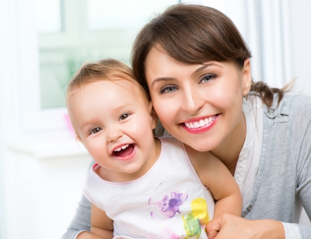mom: Happy Smiling Mother and Baby kissing and hugging at Home  Stock Photo