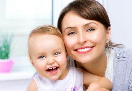 Feliz madre y bebé sonrientes besos y abrazos en el hogar