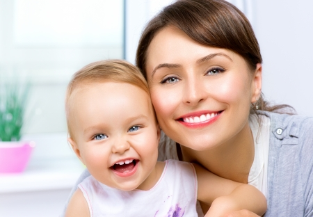mum and baby: Happy Smiling Mother and Baby kissing and hugging at Home  Stock Photo