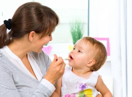 彼女はスプーンで女の赤ちゃんを授乳母
