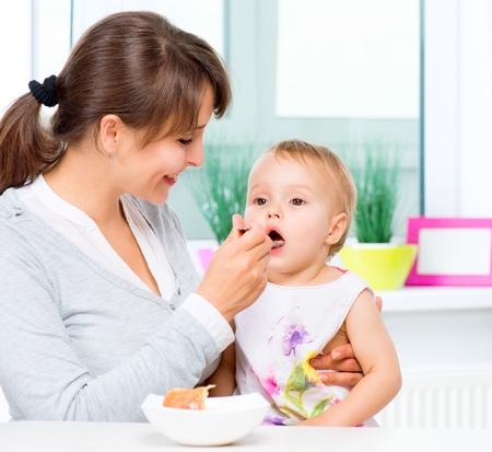 babys: Mutter füttert ihr Baby mit einem Löffel