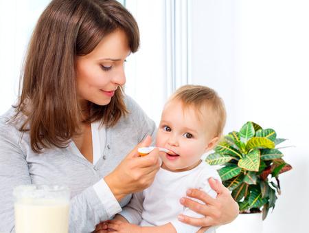 彼女はスプーンで女の赤ちゃんを授乳母 写真素材 - 22455290