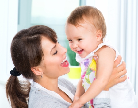 mother: Happy Smiling Mother and Baby kissing and hugging at Home