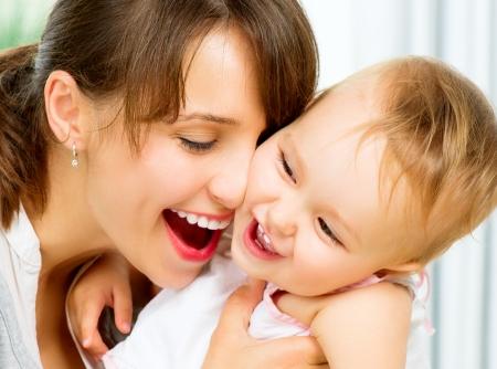 madre y bebe: Feliz madre y bebé sonrientes besos y abrazos en el hogar Foto de archivo