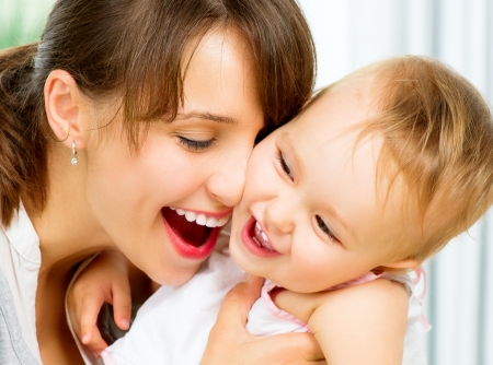 baby with mother: Happy Smiling Mother and Baby kissing and hugging at Home  Stock Photo