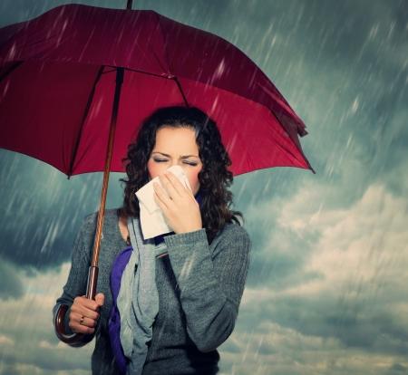 傘でくしゃみをする女性 写真素材