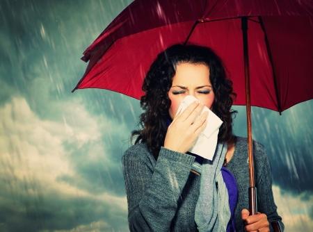秋の雨背景上の傘でくしゃみをする女性