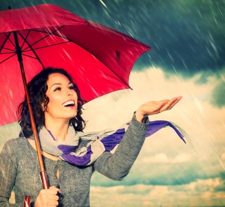 gotas de agua: Mujer sonriente con paraguas sobre fondo Autumn Rain Foto de archivo