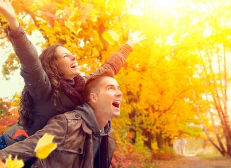 秋の公園で幸せなカップル落ちる屋外の楽しみを持っている家族 写真素材
