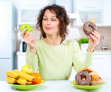 Dieting concept  Young Woman choosing between Fruits and Sweets  Banco de Imagens