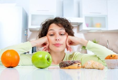 Mujer joven Dieta concepto elegir entre frutas y dulces Foto de archivo