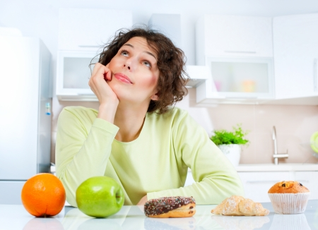 between: Dieting concept  Young Woman choosing between Fruits and Sweets  Stock Photo