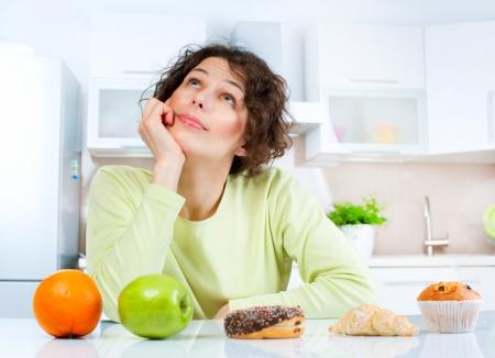 jedzenie: Koncepcja MÅ'oda diety kobieta wybierajÄ…c miÄ™dzy owoców i sÅ'odyczy Zdjęcie Seryjne