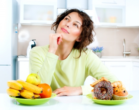 girl thinking: Dieting concept  Young Woman choosing between Fruits and Sweets  Stock Photo