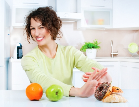 dieting: Dieting concept  Young Woman choosing between Fruits and Sweets  Stock Photo