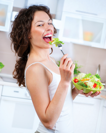 Beautiful Young Woman Eating Vegetable Salad  Dieting concept  photo