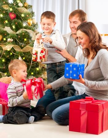 家庭: 聖誕節家庭兒童打開禮物的聖誕樹 版權商用圖片