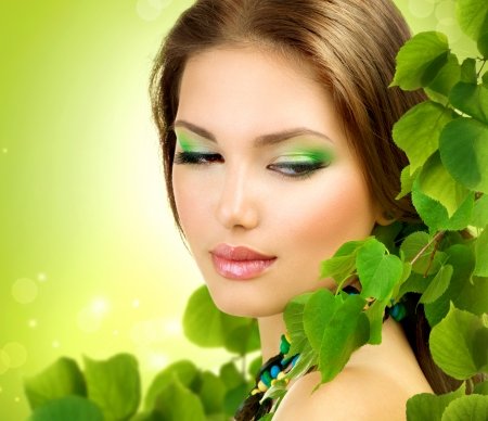 wellness woman: Beautiful Girl with Green Leaves  Spring Beauty outdoor