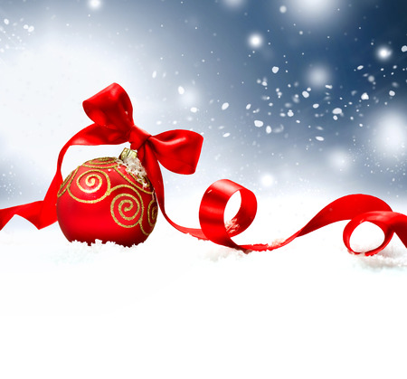 Christmas Holiday Background with Red Bauble, Ribbon, Snow and Snowflakes Stock Photo