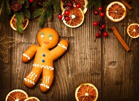weihnachten zweig: Lebkuchen-Mann �ber Holz Weihnachtsfeiertagshintergrund Lizenzfreie Bilder