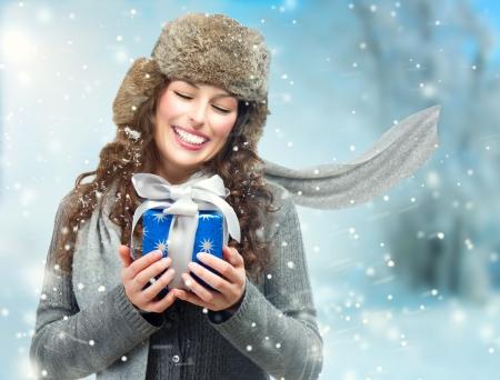 크리스마스 선물 상자와 아름 다운 젊은 여자는 여자를 놀라게했다