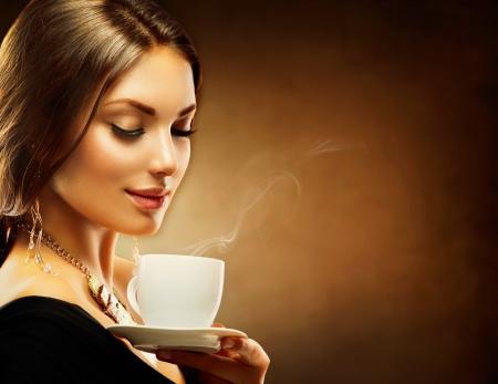 紅茶やコーヒーを飲むコーヒーの美しい少女