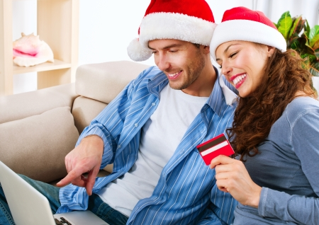 Christmas E-Shopping  Couple Using Credit Card to Internet Shop photo