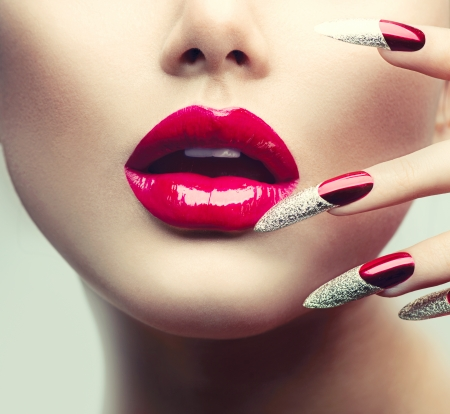 glans: Smink och manikyr Röda långa naglar och röda glansiga läppar Stockfoto