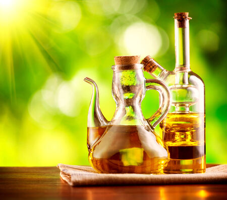 Olive Oil on the Table over Green Nature Background