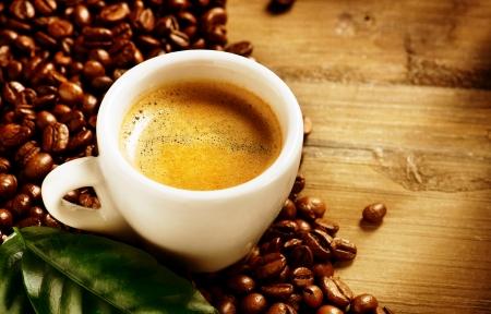 원두 커피를 커피 에스프레소 컵과 녹색 잎 스톡 콘텐츠