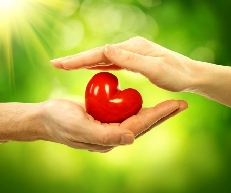 el coraz�n de san valent�n: Coraz�n de San Valent�n en el hombre y la mujer de manos sobre fondo de la naturaleza
