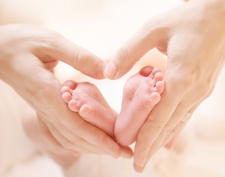 born: Tiny Newborn Baby s feet on female Heart Shaped hands closeup