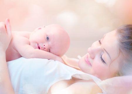 Happy Mother and her Newborn Baby Kissing and hugging Reklamní fotografie