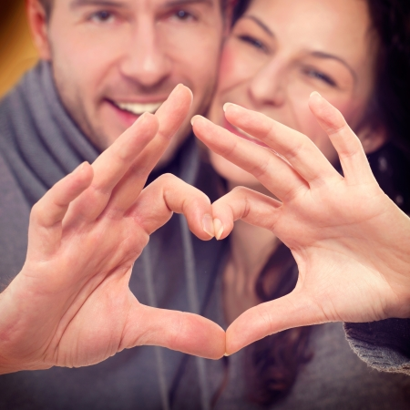 Valentine Couple Making Shape of Heart by their Hands Stock Photo