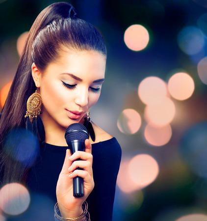 マイクを使って美しい歌う女の子美容女性 写真素材